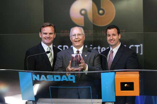 Collectors Universe CEO Michael R. Haynes (center), flanked by NASDAQ Stock Market executives Bruce Aust and Michael Beaver, holds a NASDAQ crystal commemorative plaque after the bell-ringing opening ceremony in New York City, July 22, 2005.  Photo copyright 2005, The NASDAQ Stock Market, Inc.  Reprinted with permission.