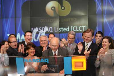 Michael R. Haynes (center), Collectors Universe C.E.O., happily signs his name after opening NASDAQ trading on July 22, 2005.  Photo copyright 2005, The NASDAQ Stock Market, Inc.  Reprinted with permission.