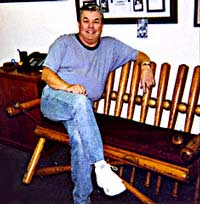 Dave Ariss sits on his one of a kind<br>baseball memorabilia bench.