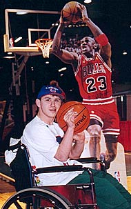 A young man in front of a cut-out of Michael Jordan on the court.
