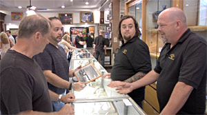 A customer (left) watches as autograph expert Steve Grad of PSA/DNA Authentication Services discusses an item in hand with Austin 'Chumlee' Russell and Rick Harrison of the popular 'Pawn Stars' television program.  (Photo courtesy of Left Field Pictures.)